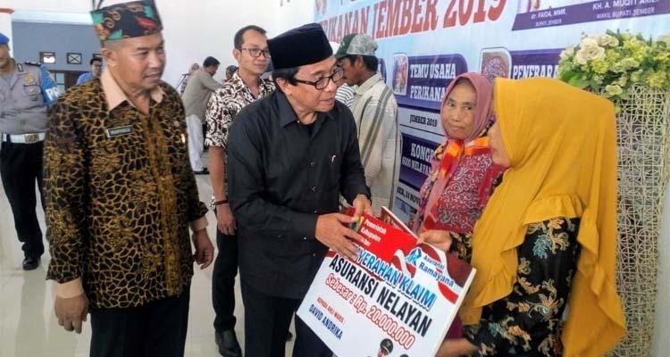 Wakil Bupati Jember KH Muqit Arief menyerahkan kartu asuransi kepada keluarga nelayan Puger. (rir)