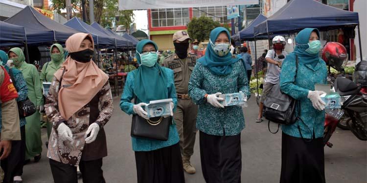BAGIKAN MARKER: Pembagian masker kepada para pedagang dan pengunjung di Pasar Tanjung