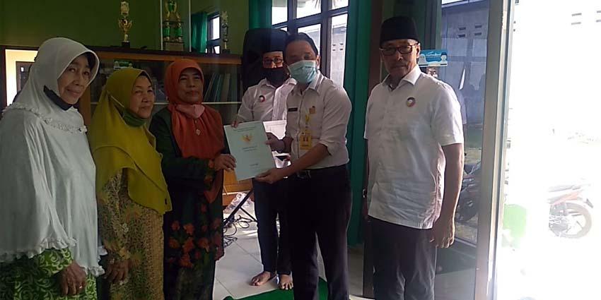 Ketua PC Muslimat Emi Kusminarni NU saat menerima sertifikat dari Kepala Kantor Pertanahan Jember Sugeng